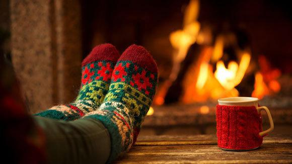 Person wearing holiday socks in front of a fireplace