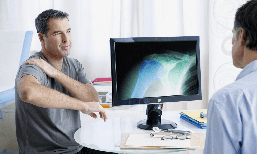 Shoulder doctor discussing pain with patient