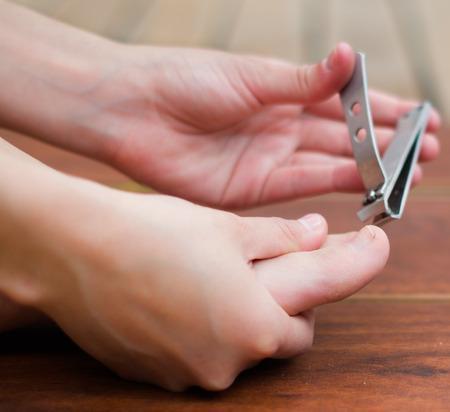 hand holding toenail clipper on toe