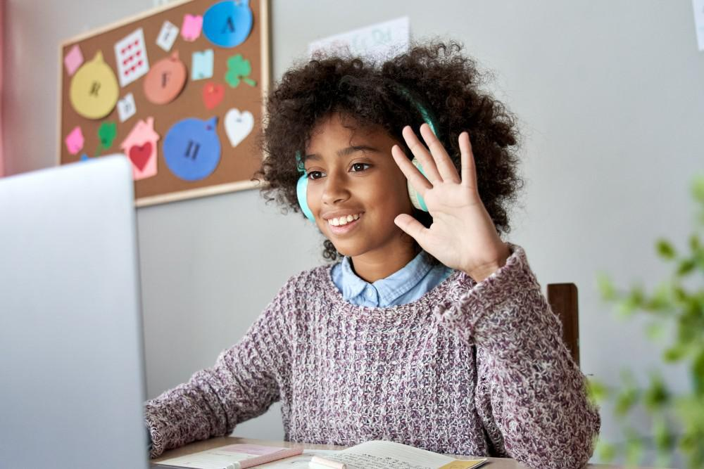 Child Raising Her Hand in Front of Computer