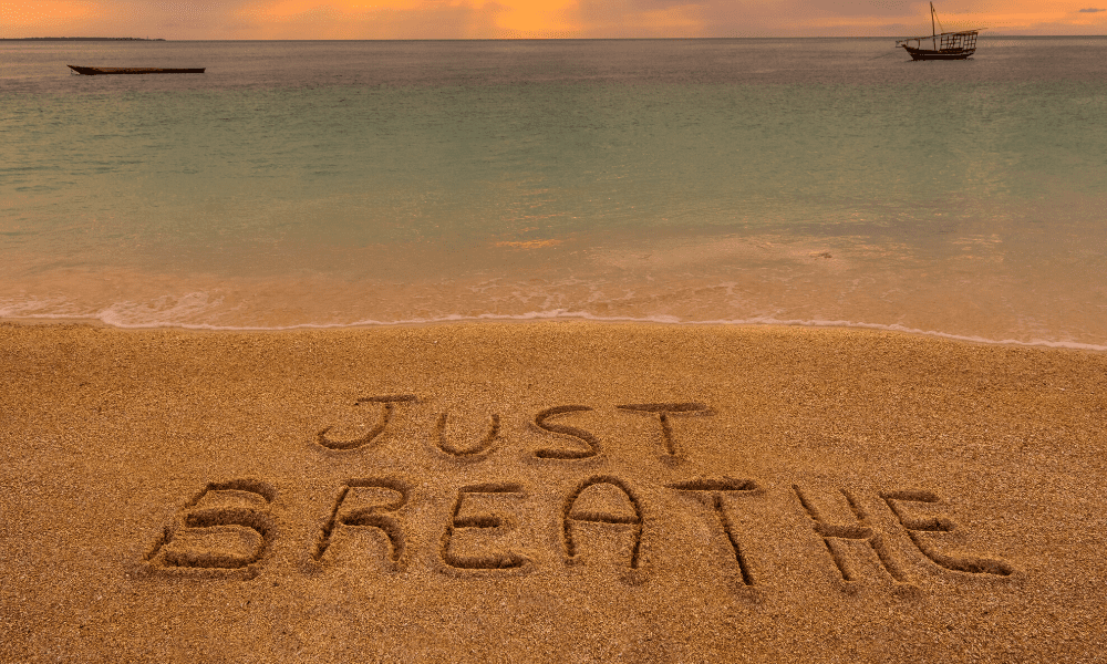 picture of the words Just Breathe on a beach in the sand with water in the background