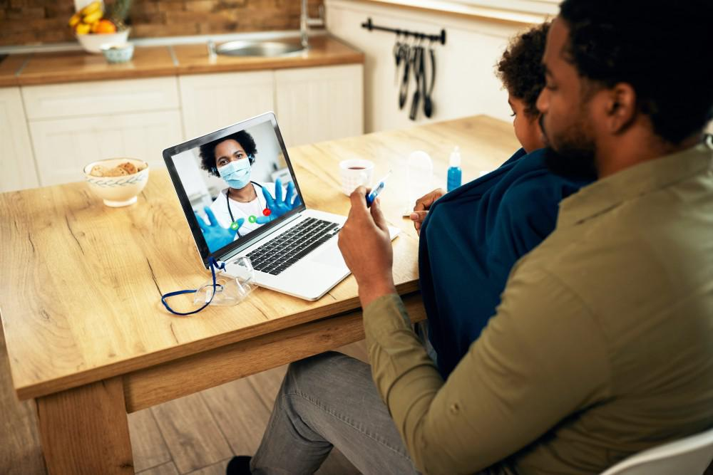 Father and son talk to their doctor via Telemedicine from home