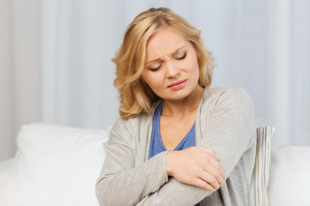 Middle-age woman holding sore elbow.