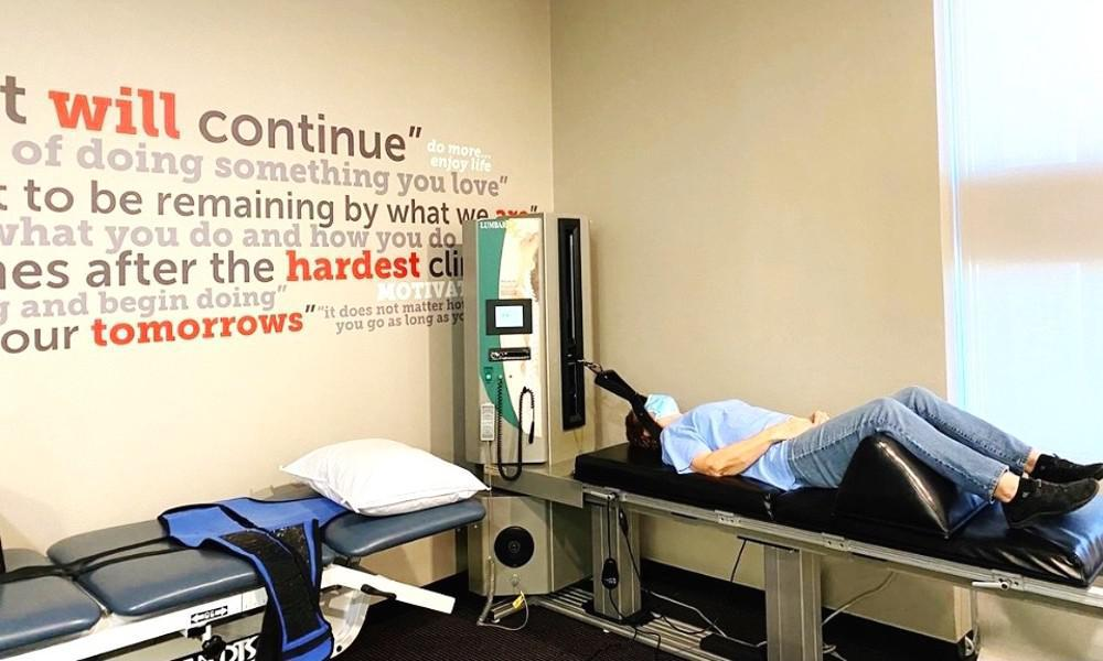 Woman laying on chiropractic table doing spinal decompression