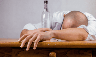 Drunk man lying on a table