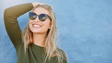 young woman with sunglasses smiling in the sun